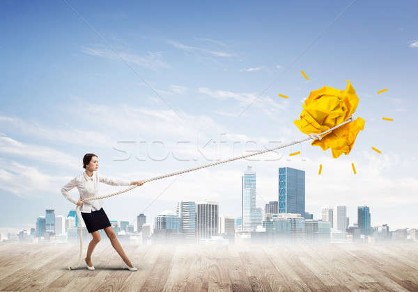 Businesswoman pulling paper ball with rope and making it raise up Stock photo © adam121