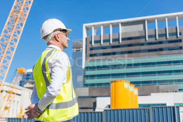 Senior foreman in glasses doing his job at building area on sunny day Stock photo © adam121