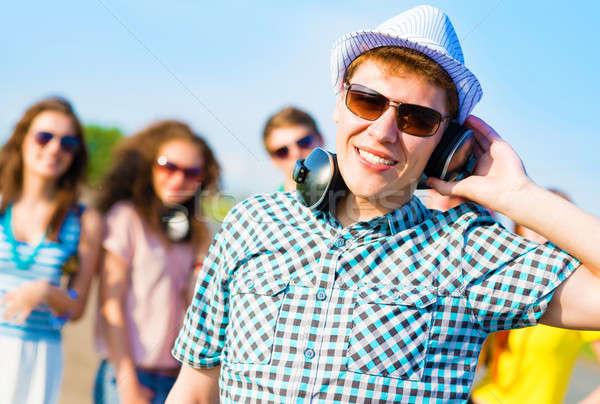 Moço óculos de sol fones de ouvido mão blue sky amigos Foto stock © adam121