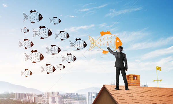 Businessman standing with back on house brick roof and drawing. Mixed media Stock photo © adam121
