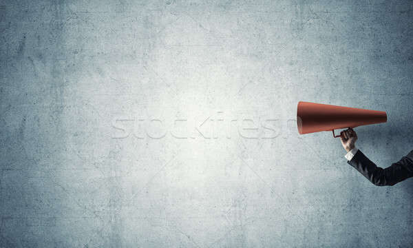 Hand of businesswoman holding red paper trumpet against concrete Stock photo © adam121