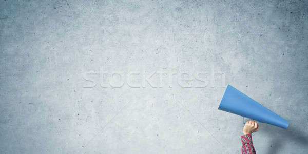Hand of woman holding paper trumpet against concrete background Stock photo © adam121