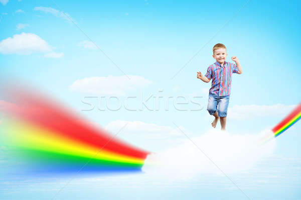 boy jumping on clouds and a rainbow Stock photo © adam121