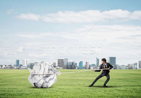Stock photo: Man pulling with effort big crumpled ball of paper as creativity