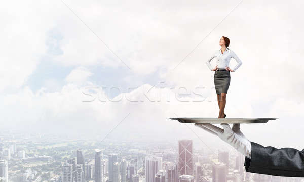 Confident elegant businesswoman presented on metal tray against cityscape background Stock photo © adam121