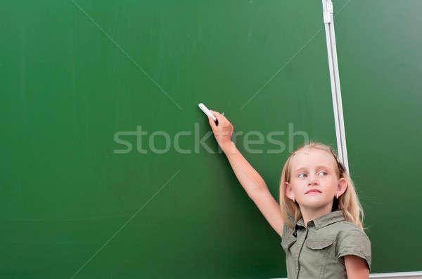 Schoolgirl writing on a blackboard Stock photo © adam121