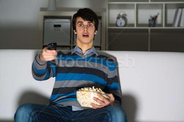Młody człowiek oglądanie telewizji popcorn pilota telewizji film Zdjęcia stock © adam121