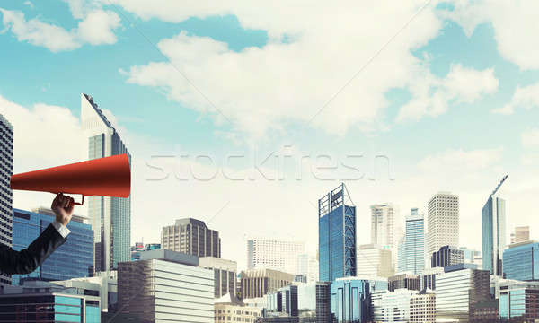 Hand of businesswoman holding red paper trumpet against cityscape background Stock photo © adam121