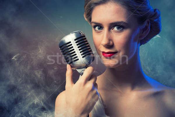 Mujer atractiva cantante micrófono detrás resumen moda Foto stock © adam121
