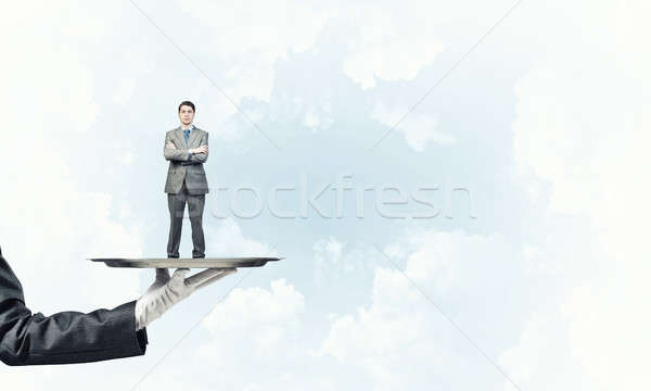 Confident businessman presented on metal tray against blue sky b Stock photo © adam121