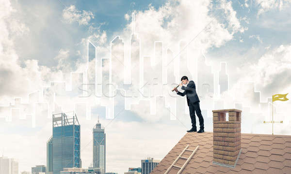 Engineer man standing on roof and looking in spyglass. Mixed med Stock photo © adam121