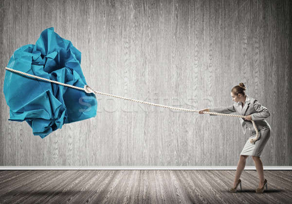 Woman pulling with effort big crumpled ball of paper as creativi Stock photo © adam121