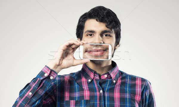 человека мобильного телефона молодым человеком смартфон улыбка Сток-фото © adam121