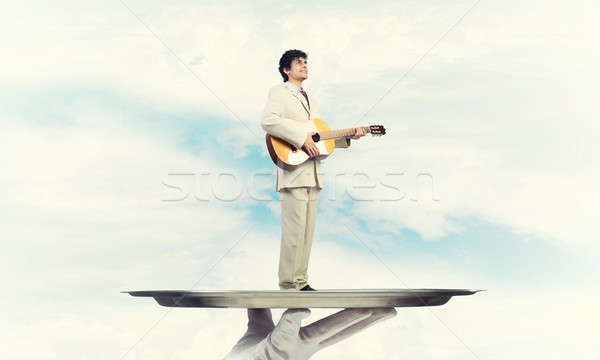 Businessman on metal tray playing acoustic guitar against blue s Stock photo © adam121