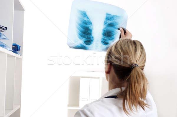 Female medic looking at x-rays Stock photo © adam121