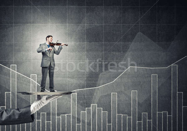 Businessman on metal tray playing violin against graphs and diag Stock photo © adam121