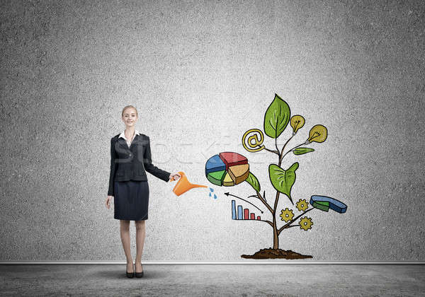Young businesswoman in empty room watering drawn growth concept with can Stock photo © adam121