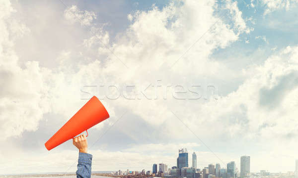 Hand of man holding red paper trumpet against cityscape backgrou Stock photo © adam121
