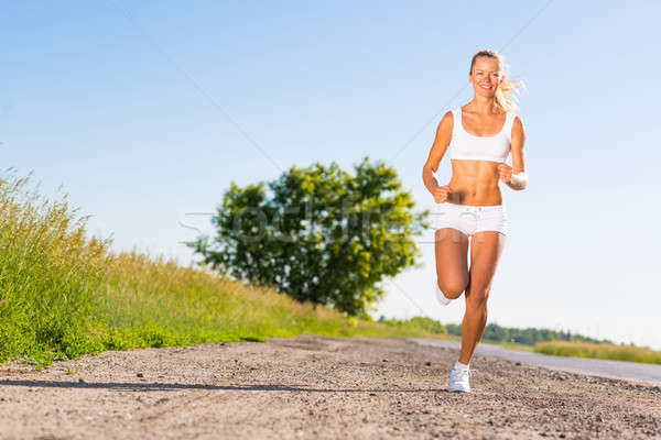 young athletic woman running on the road Stock photo © adam121