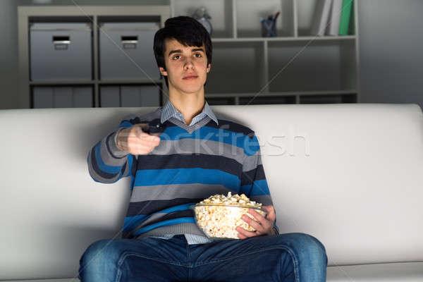 Fiatalember tv nézés pattogatott kukorica távirányító televízió film Stock fotó © adam121