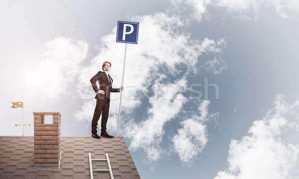 Young businessman with parking sign standing on brick roof. Mixe Stock photo © adam121