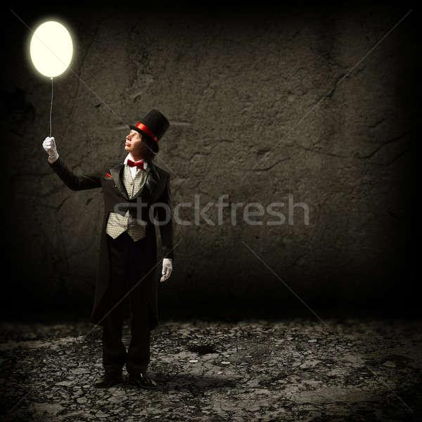 magician holding a glowing balloon Stock photo © adam121