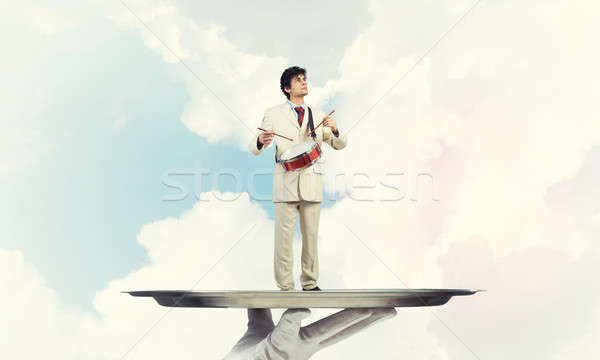 Young businessman on metal tray playing drums against blue sky b Stock photo © adam121
