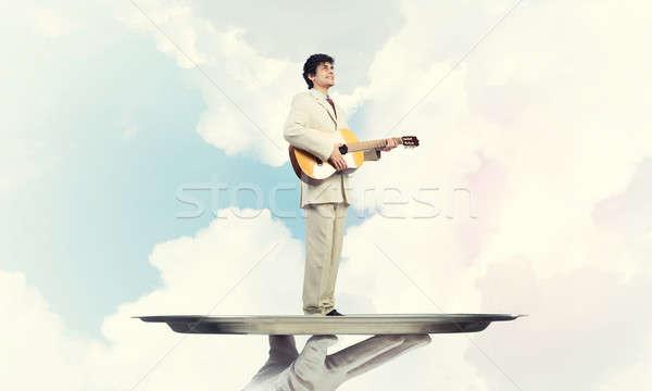 Işadamı Metal tepsi oynama akustik gitar mavi Stok fotoğraf © adam121