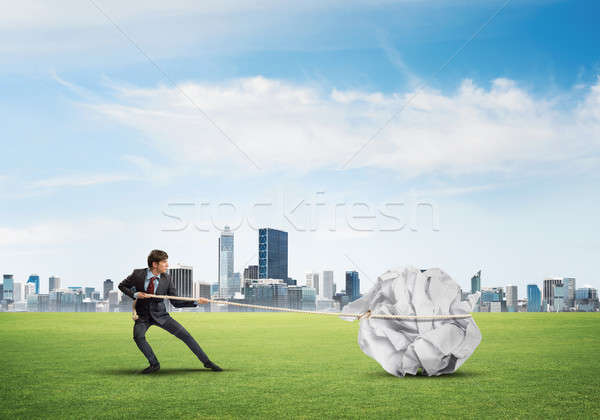 Man pulling with effort big crumpled ball of paper as creativity sign Stock photo © adam121