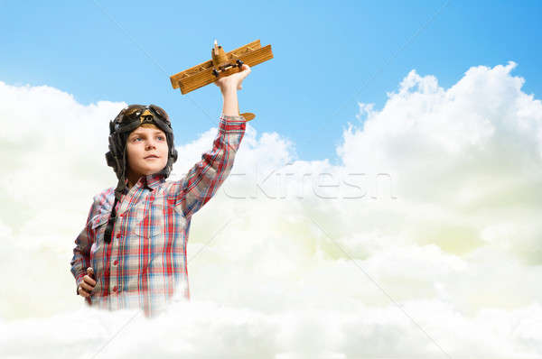 Stock photo: Boy in helmet pilot playing with a toy airplane