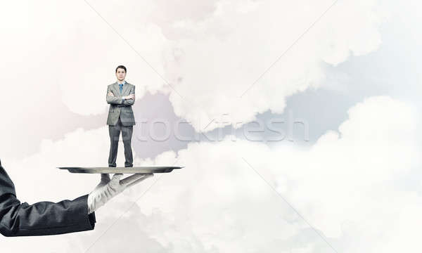 Confident businessman presented on metal tray against blue sky b Stock photo © adam121