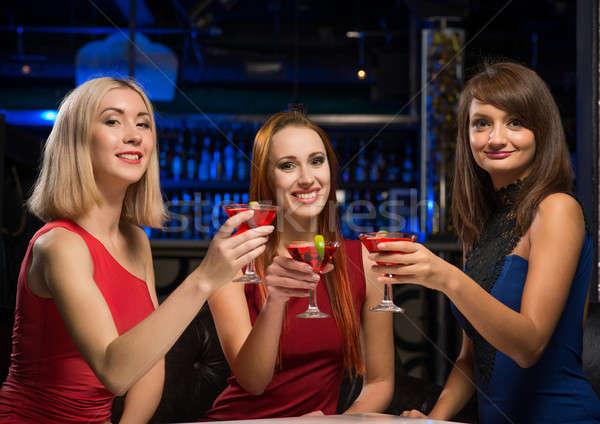 three girls raised their glasses in a nightclub Stock photo © adam121
