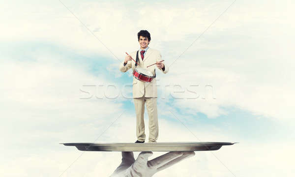 Stock photo: Young businessman on metal tray playing drums against blue sky background