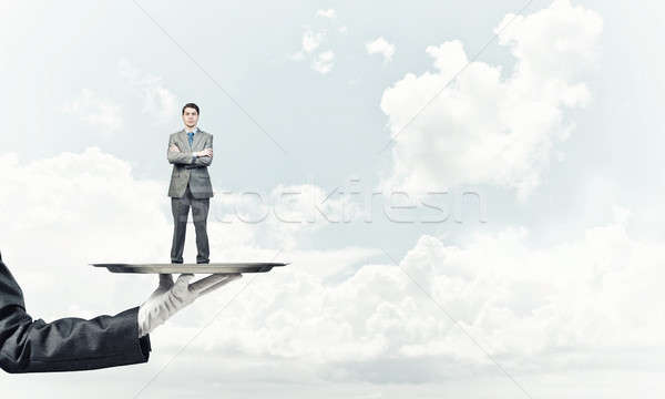Confident businessman presented on metal tray against blue sky background Stock photo © adam121