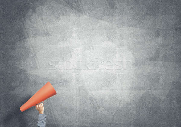 Hand of man holding paper trumpet against concrete background Stock photo © adam121