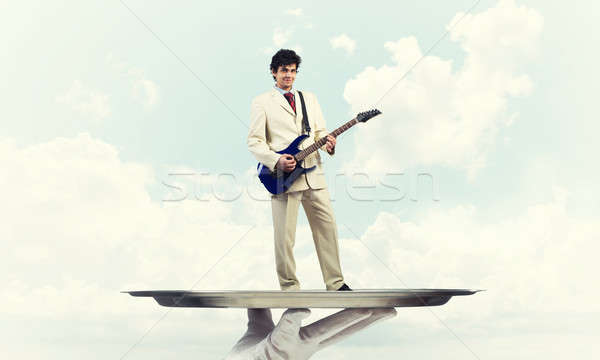 Businessman on metal tray playing electric guitar against blue s Stock photo © adam121