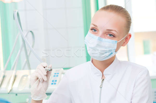 female dentists in protective mask holds a dental drill Stock photo © adam121