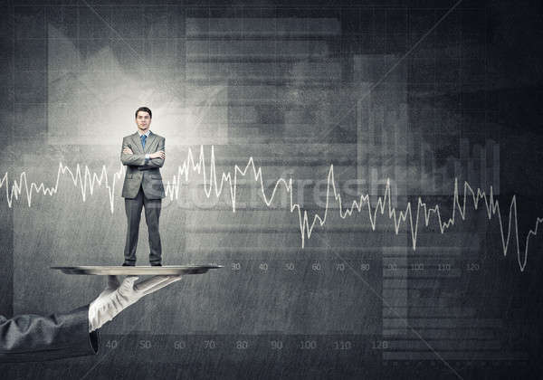Confident businessman presented on metal tray against graphs and diagrams background Stock photo © adam121