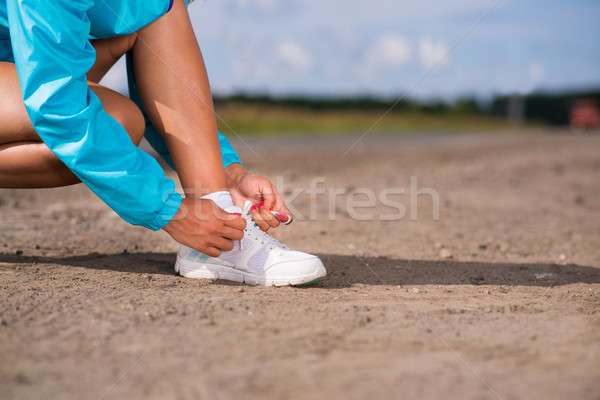 Stock photo: young woman tying shoelaces on sneakers