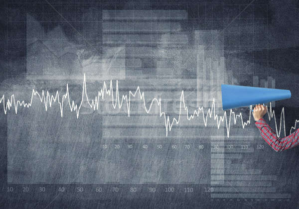 Hand of woman holding blue paper trumpet against graphs background Stock photo © adam121