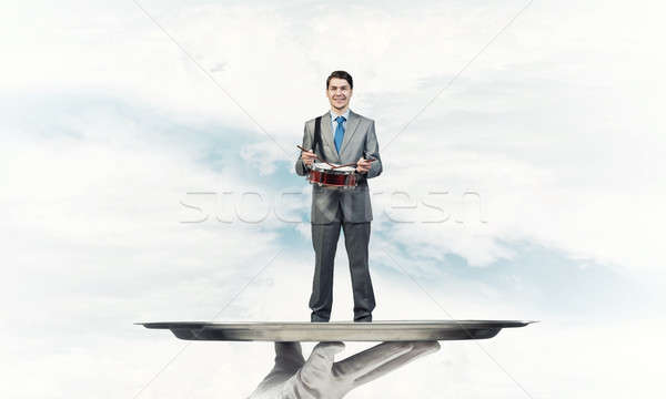 Businessman on metal tray playing drum blue sky background Stock photo © adam121