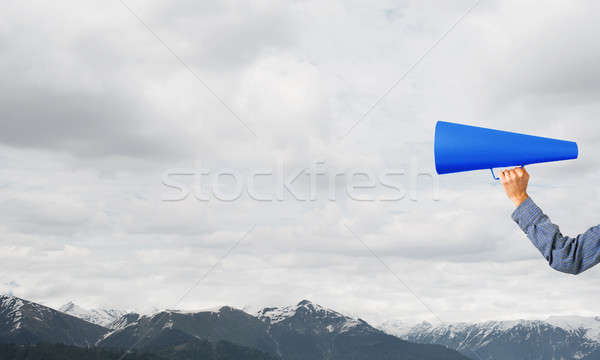 Hand of man holding paper trumpet against natural landscape background Stock photo © adam121