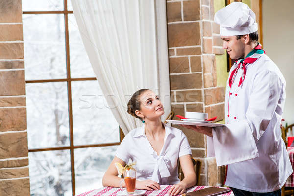 Chef brings a dish pretty woman in a restaurant Stock photo © adam121