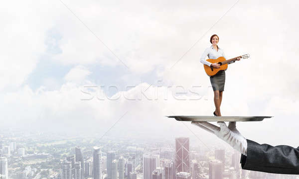Attractive businesswoman on metal tray playing acoustic guitar against cityscape background Stock photo © adam121
