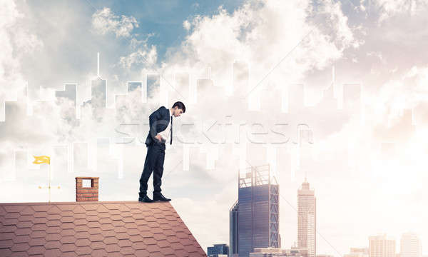 Biznesmen patrząc w dół dachu nowoczesne Cityscape młodych Zdjęcia stock © adam121