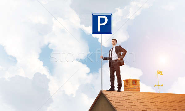 Young businessman with parking sign standing on brick roof. Mixed media Stock photo © adam121