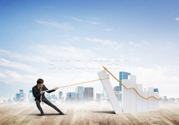 Stock photo: Man pulling with effort big pulling rope graph, as a symbol of financial growth