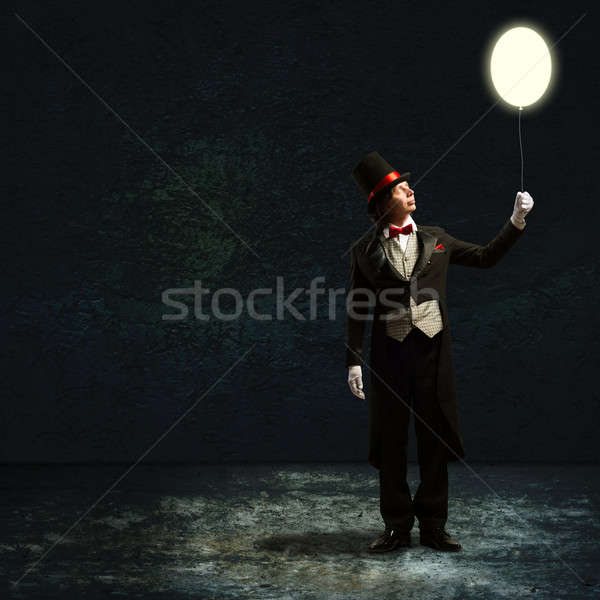 magician holding a glowing balloon Stock photo © adam121