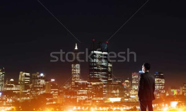 Businessman viewing night glowing city Stock photo © adam121