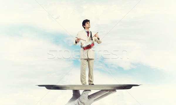 Young businessman on metal tray playing drums against blue sky background Stock photo © adam121
